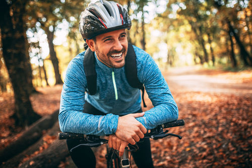 Cosmetic dental implants | man smiling on bicycle