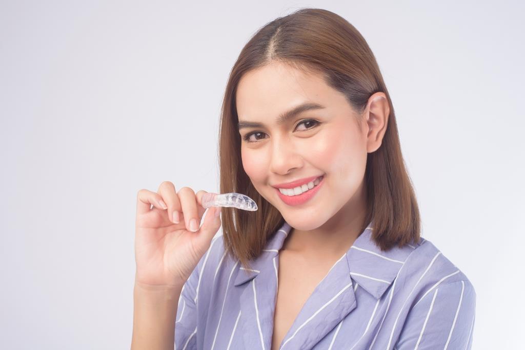family dentist Bethesda | Happy woman holding invisalign aligners.
